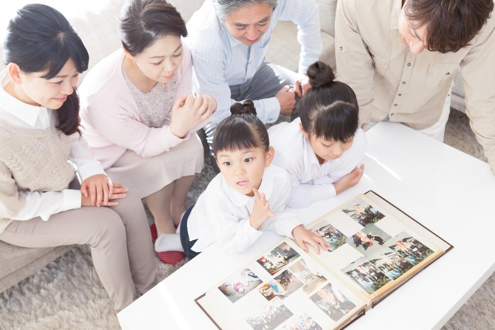 家族で昔のアルバムを見返すイメージ