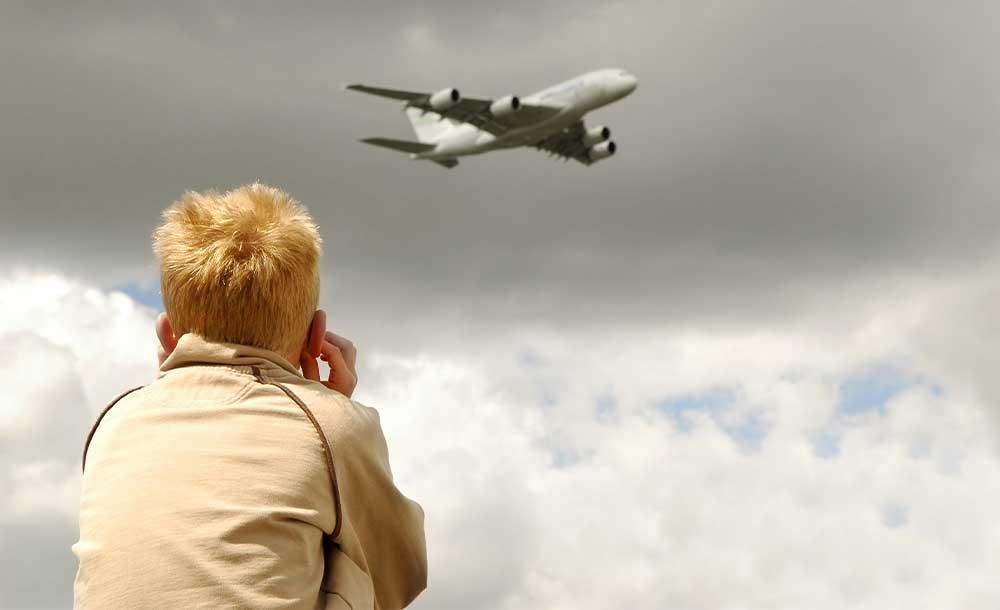 飛行機の轟音に耳をふさぐ子ども。騒音は大人だけでなく、子供の健康、学力にまで影響します。